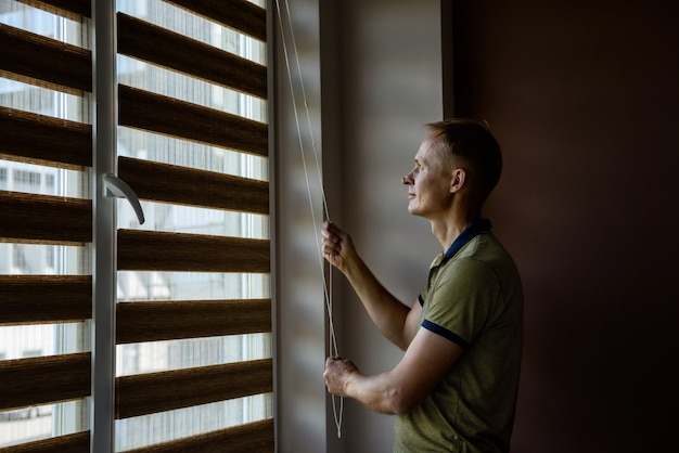 The man is opening  the blinds.