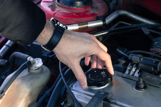 男は車のエンジンからオイルキャップを開けています。