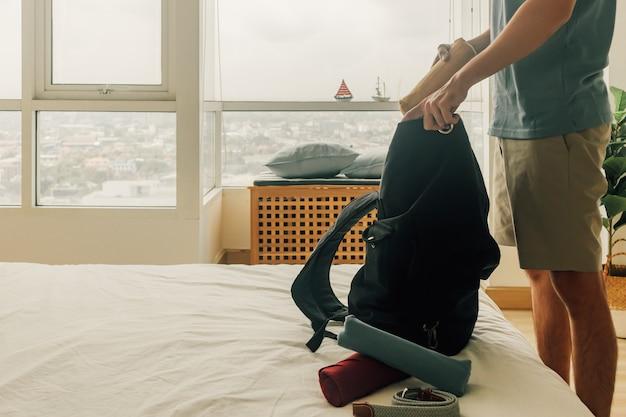 男は旅行の準備ができて彼のバックパックを詰めています。