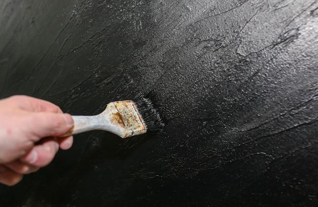 남자는 붓으로 검은 배경을 칠하고 있다. 벽에 예술입니다. 노동자 손가락과 석고. 추상적이고 세련된 수리.