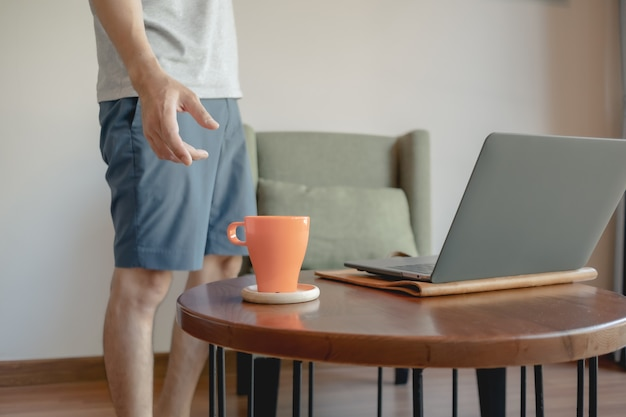 Man is picking up an orange coffee cup while working on his laptop.