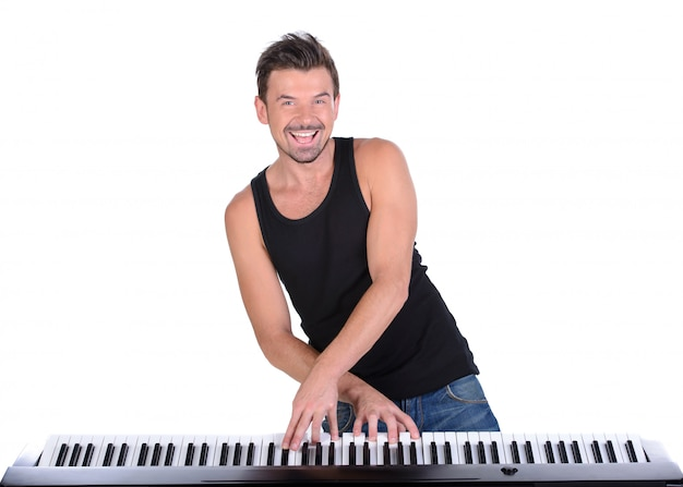 Man is playing digital piano and smile.
