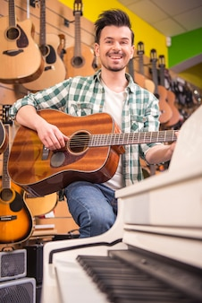 Man is playing on guitar at music shop.