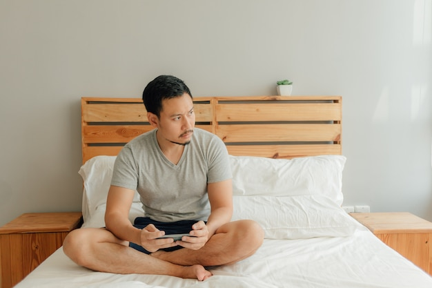 Man is playing mobile game with his smartphone on the bed.