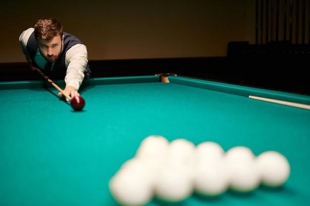 Мужчина играет в снукер, он стремится бросить снукер. красивый парень держит руки на бильярдном столе. бильярд