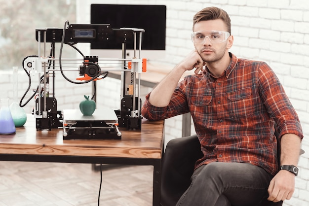 A man is posing near the 3d printer.