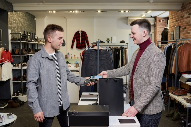 A man is posing while using a smartphone to pay by wireless nfc technology for purchases in a clothing store. a smiling shop assistant is holding out a terminal for contactless paying to a customer