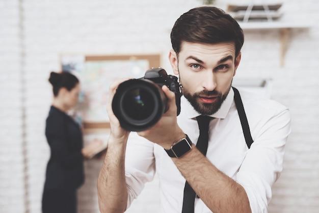 남자는 카메라와 함께 포즈, 여자는 단서지도를보고있다.