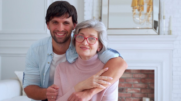 Man is posing with his mother at her home.