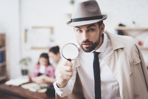 Man is posing with magnifying glass.