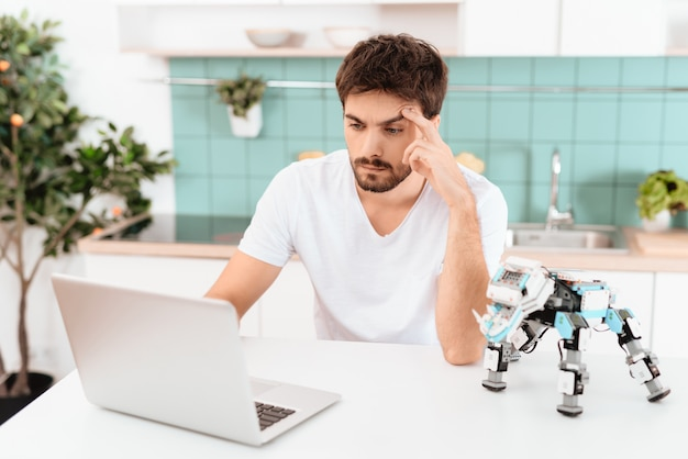A man is programming a robot in the kitchen