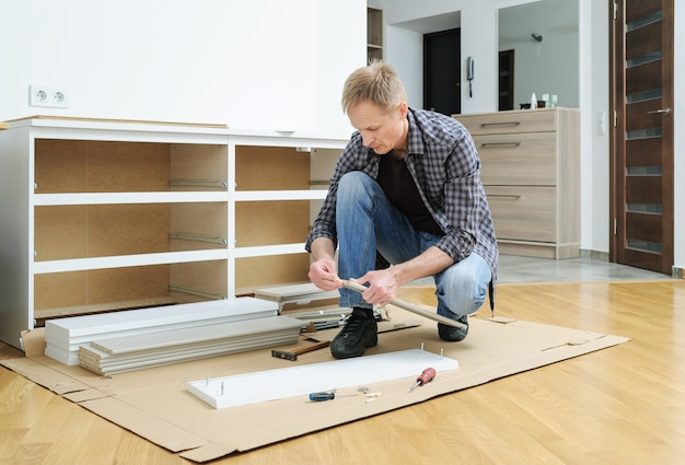 The man is pushing a wooden pin into a furniture board
