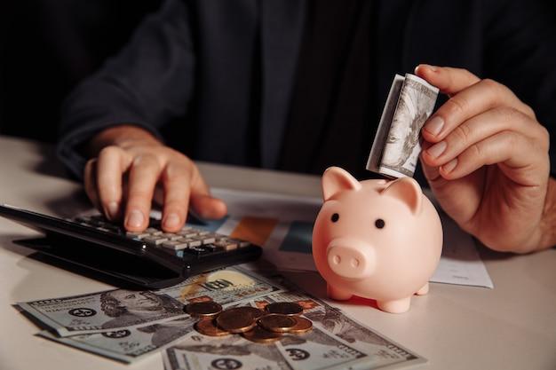 男はピンクの貯金箱にドル紙幣を入れています