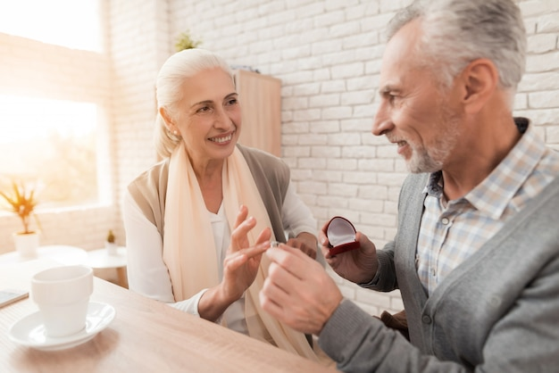 Man is putting engagement ring on hand of mature woman.