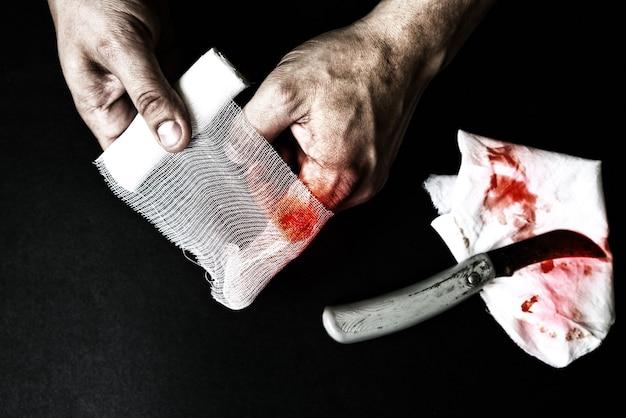 남자가 상처에 붕대를 감고 있다. 출혈 부상. 칼로 깊게 자릅니다.