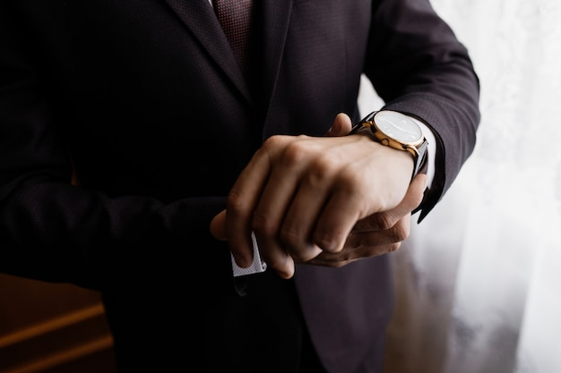 Man is putting a watch on his wrist
