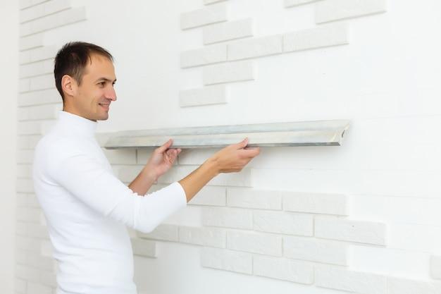 Мужчина кладет белые плитки на серый бетон. ремонтные работы ремонт в квартире. реставрация пузырьковым уровнем в помещении. работа в процессе. мужчина держит в руках уровень.