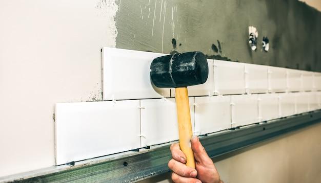 男はハンマーの助けを借りて灰色のコンクリートに白いタイルを置いています。メンテナンス修理はフラットで改修工事を行います。屋内での修復。男はブラシとパレットナイフで表面を下塗りしています。