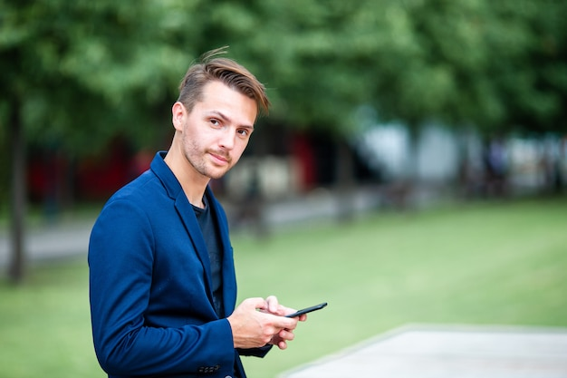 Man is reading text message on mobile phone while walking in the park