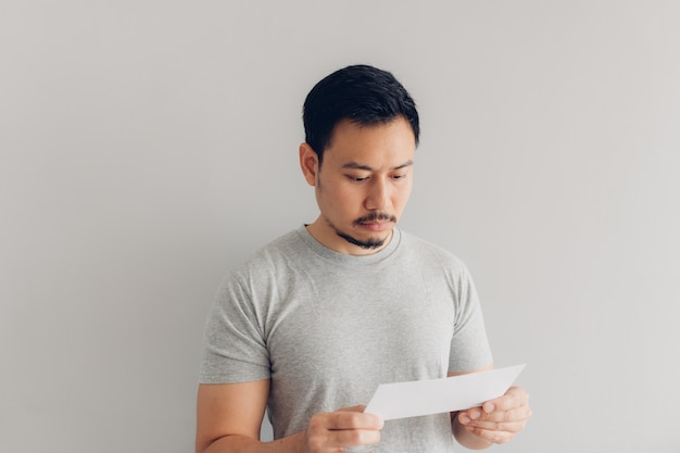 Man is reading the white mail message or the bill.