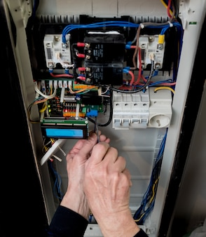 The man is repairing the switchboard voltage with automatic switches.