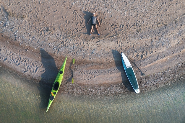 The man is resting on the beach. a kayak and a paddleboard are moored to the shore. aerial view