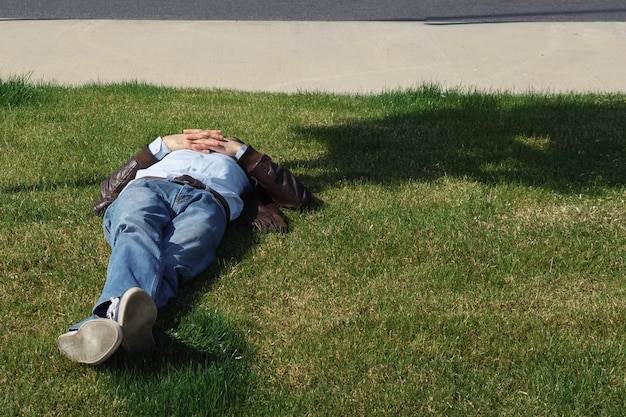 Man is resting on the lawn on a sunny day