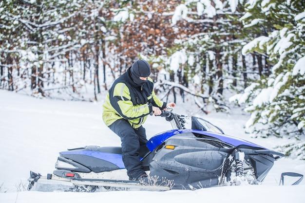 男は山でスノーモービルに乗っています