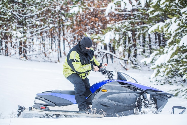 Man is riding snowmobile in mountains