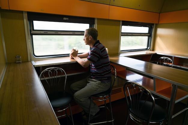 A man is riding in a train restaurant car.