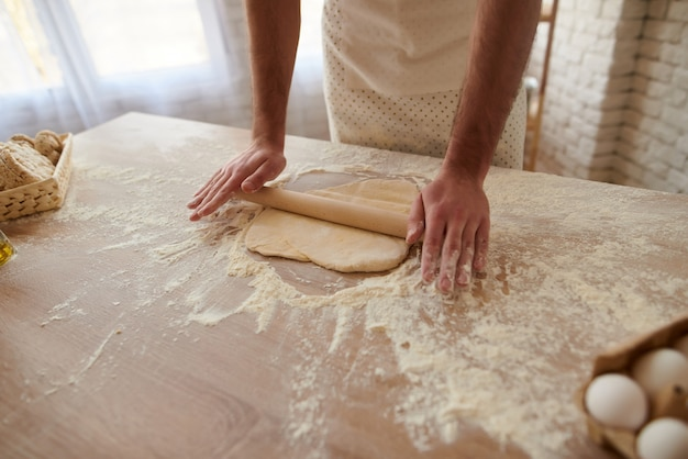 Man is rolling out dough on kitchen table.