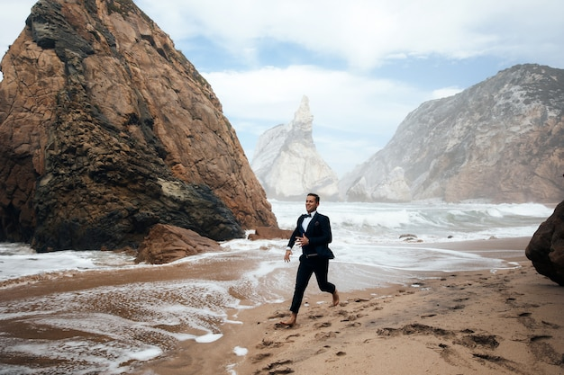 Man is running on the wet sand among the rocks
