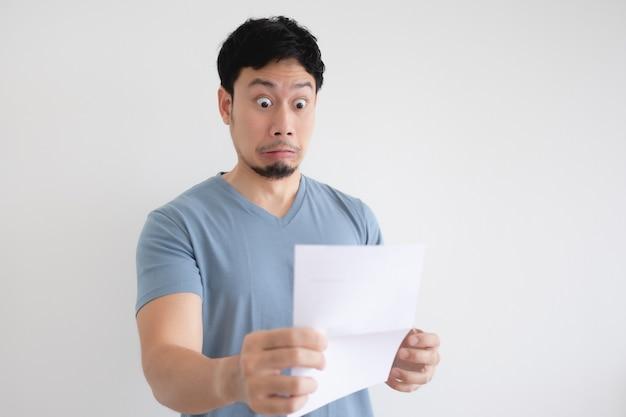 Человек грустен и шокирован письмом в руке на изолированном фоне.