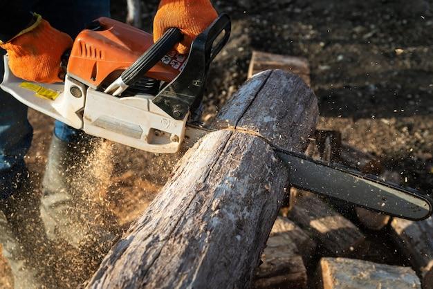 Мужчина распиливает большое бревно бензопилой, крупным планом, заготавливает дрова