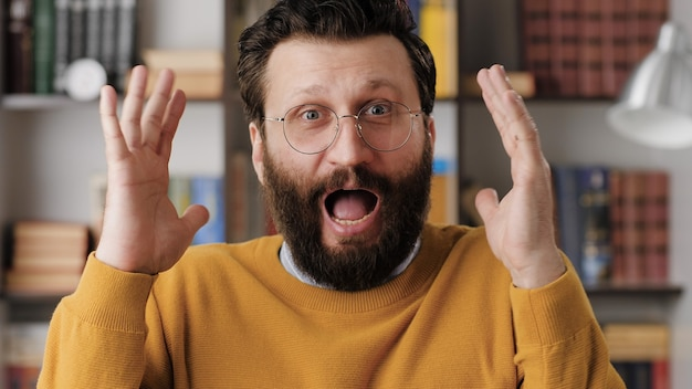 남자는 무서워, 겁에 질려. 사무실이나 아파트에 있는 안경을 쓴 겁에 질린 수염이 난 남자는 갑자기 손을 들고 카메라를 쳐다보며 매우 무섭고 겁에 질려 있습니다. 클로즈업 보기
