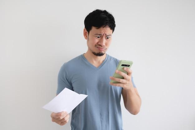 男は法案と孤立した壁のスマートフォンで真剣です。