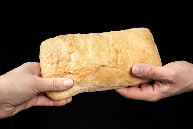 Man is sharing fresh bread ciabatta on black background. two hands.