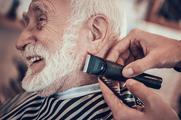 Man is shaving grey haired adult male with razor
