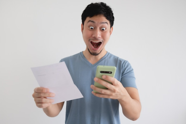 Man is shocked by the bill and the smartphone on isolated wall.