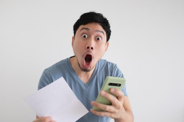 Человек шокирован счетом и смартфоном на изолированном фоне.