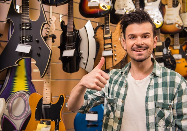 Man is showing thumb up in electric guitars store