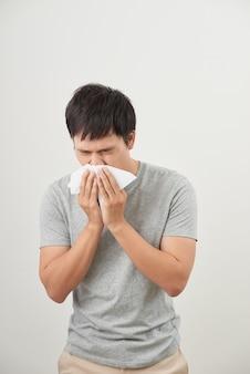 Мужчина болен и чихает на белом фоне, азиатский