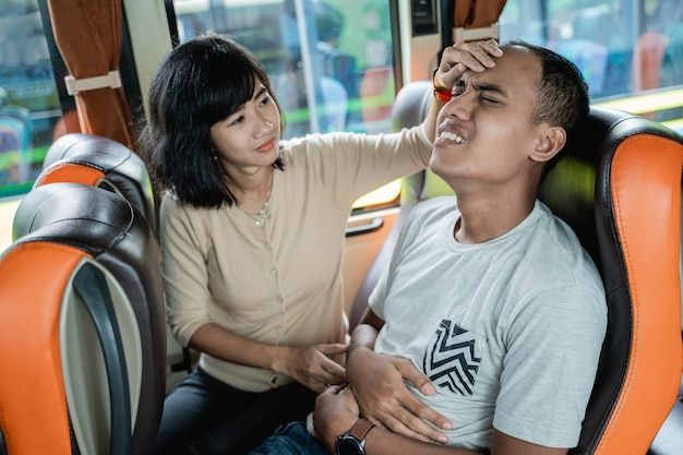 A man is sick and a woman holds her forehead while sitting on a bus bench while traveling