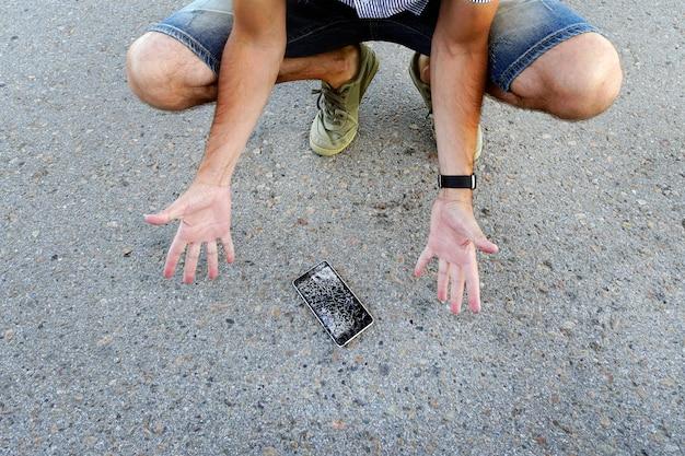 男は座って、ひびの入った画面で壊れたスマートフォンを持っています。男は携帯電話をアスファルトに落とし、壊した。壊れた携帯電話で欲求不満の男。