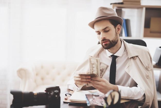 男はお金を数えるテーブルに座っています。