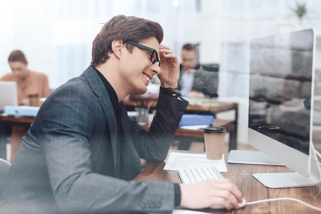 남자는 컴퓨터에 앉아 일하고 있습니다.