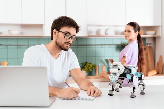 男は台所のテーブルに座って、ロボットをプログラミングしています。