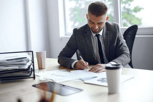 男はテーブルに座っています。ビジネススーツを着た男。ビジネスマンは、ドキュメントに署名します