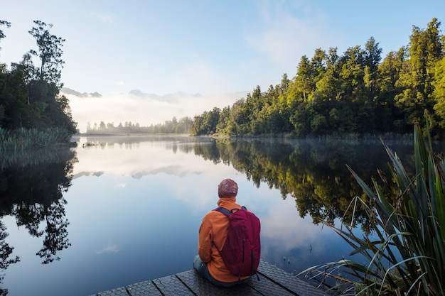 A man is sitting at ease by the calm lake. relaxation vacation