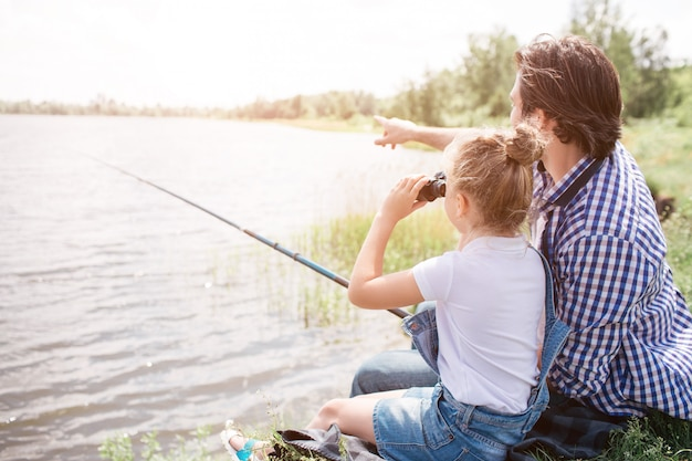 Man is sitting on grass near water with his daughter and pointing forward. girl is looking there through binoculars. he is holding fish-rod in hands.